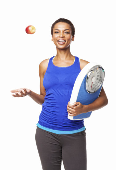 Portrait of a fit African American woman tossing an apple while holding a weighing scale. Vertical shot. Isolated on white.